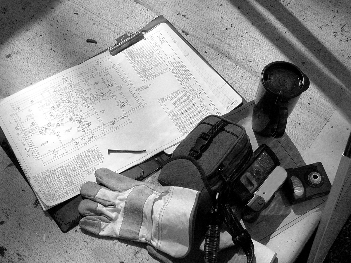 Black and White Shot of construction plans and tools
